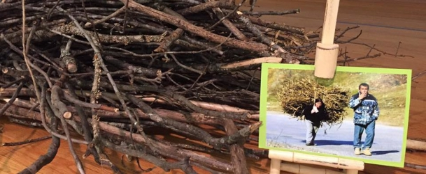 A photo and a bundle of sticks that demonstrate the work that woman have to do simply to feed their families.